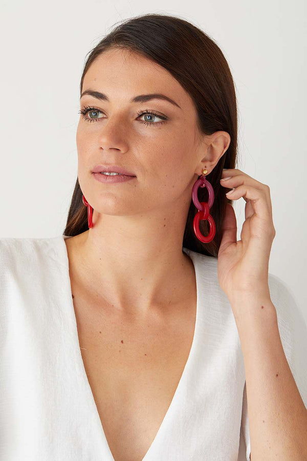 Red pink statement earrings worn by a model in a in a white blazer