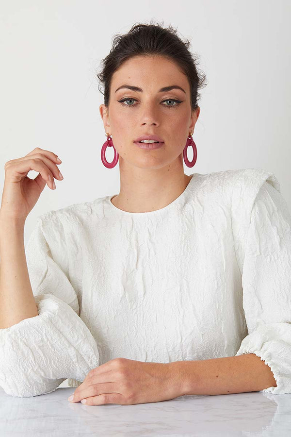 a pair of luxury italian pink statement earrings made of resin worn by a model in a white textured crew neck top