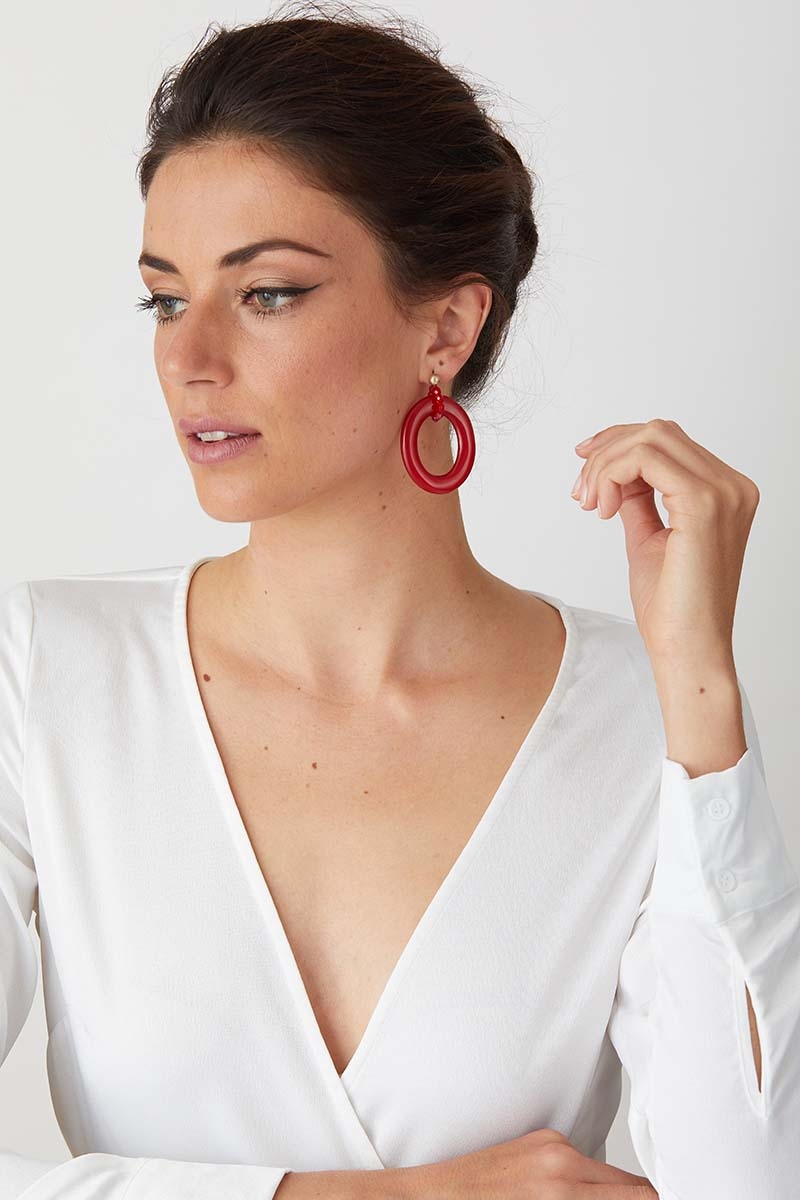 Red candy apple statement earrings worn by a model in a white low cut top