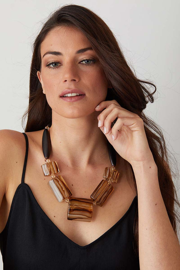 Animalier brown statement necklace worn by a model in a black evening dress