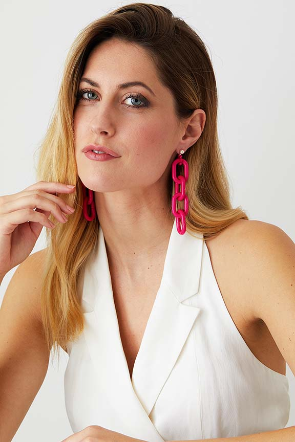 Hot pink chain hoop statement earrings worn by a model in a white double-breasted blazer