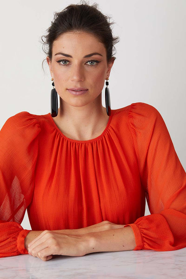 Black statement earrings worn by a model in a flowy colourful dress