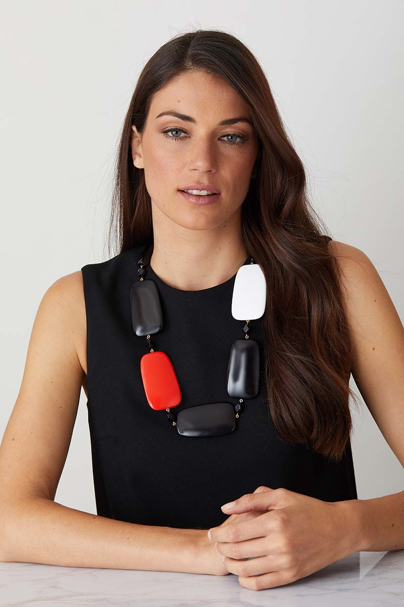 Black white red statement necklace worn by a model in a black evening dress