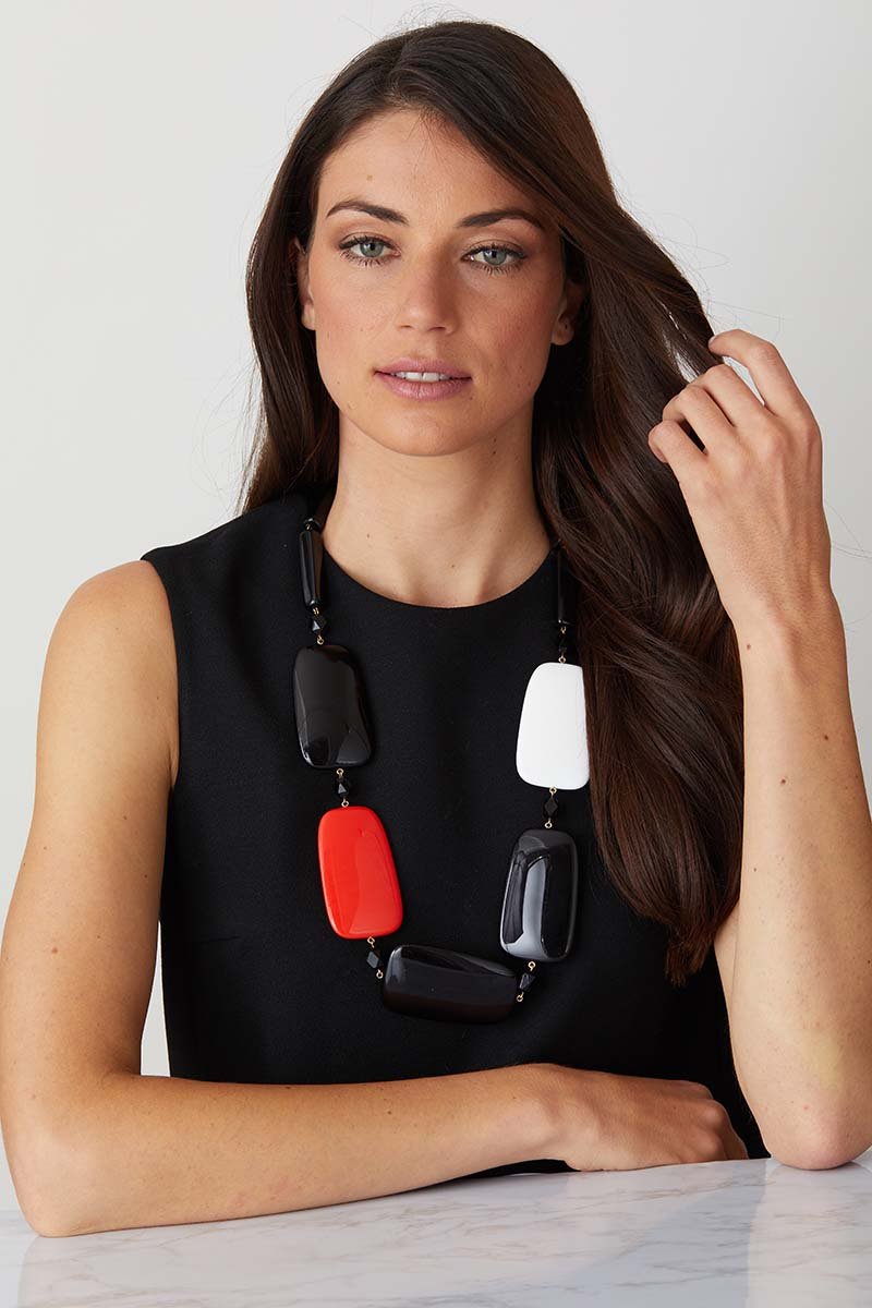 Black white red resin fashion necklace worn by a model in a black evening dress
