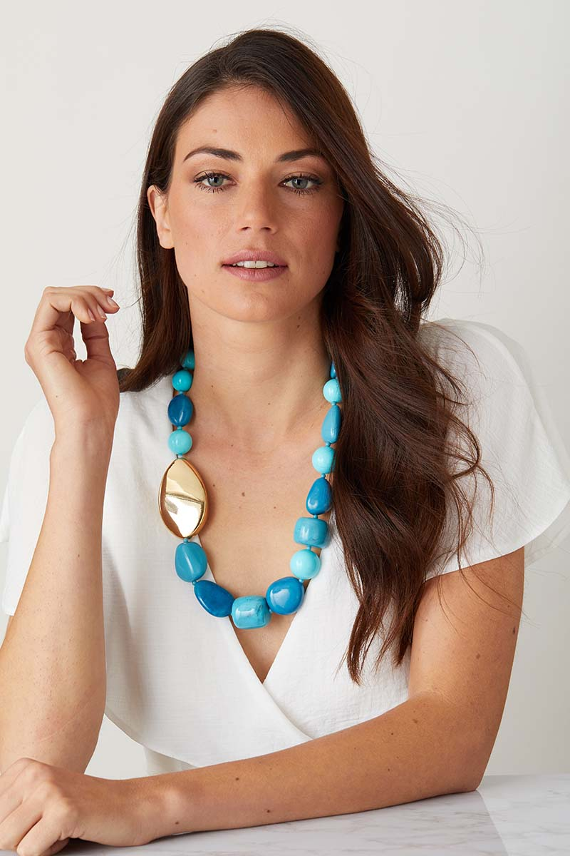 Blue turquoise gold statement necklace worn by a model in a white flowy top