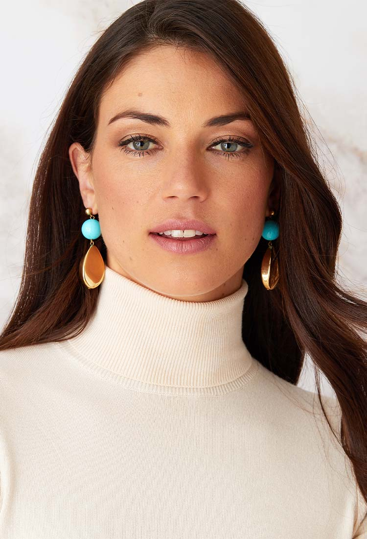 Blue gold statement earrings worn by a model in a white turtleneck
