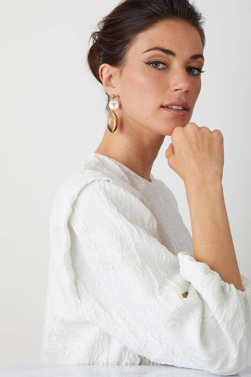Orange gold statement earrings worn by a model in a high fashion white top