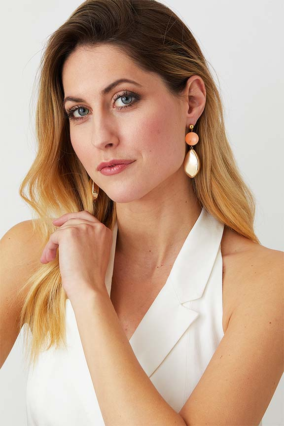 Pink burl gold statement earrings worn by a model in a white double-breasted suit blazer