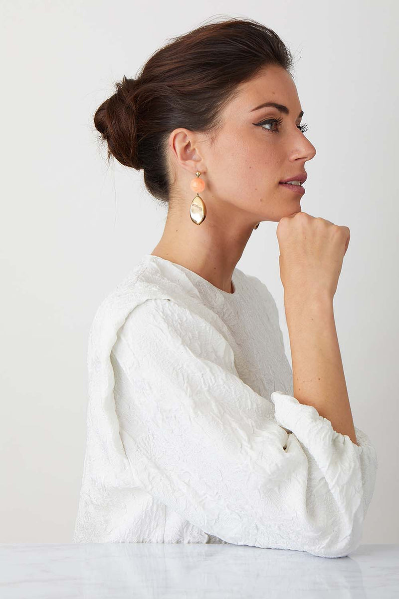 Pink burl gold statement earrings worn by a model in a white top