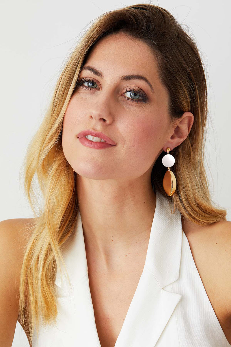 White gold statement earrings worn by a model in a white top