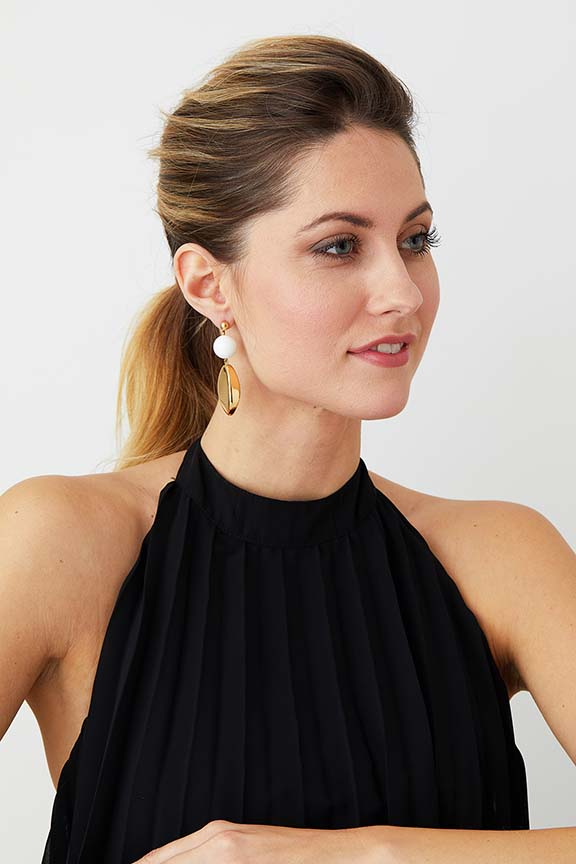 White gold statement resin earrings worn by a model in a black pleated evening dress