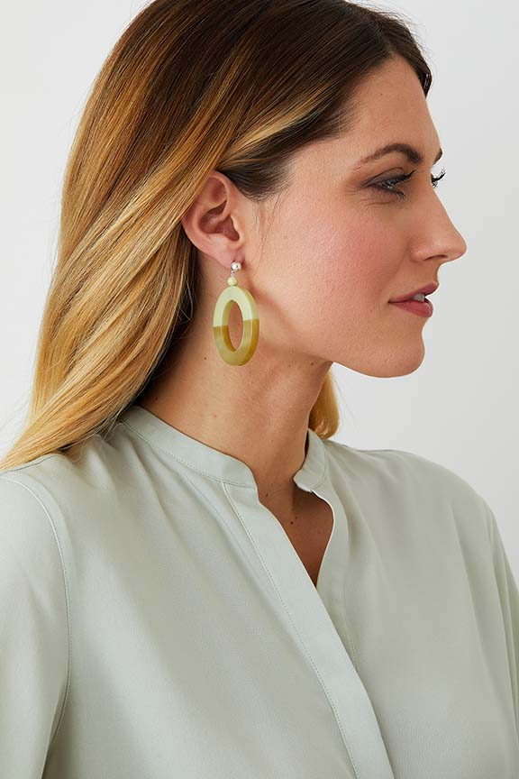 Green pastel hoop statement earrings worn by a model in a  green top