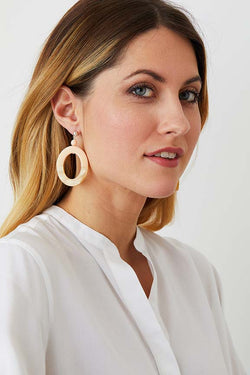 Pink pastel cream hoop statement earrings worn by a model in a white tunic