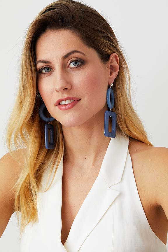 Geometric Blue resin statement earrings worn by a model in a white top