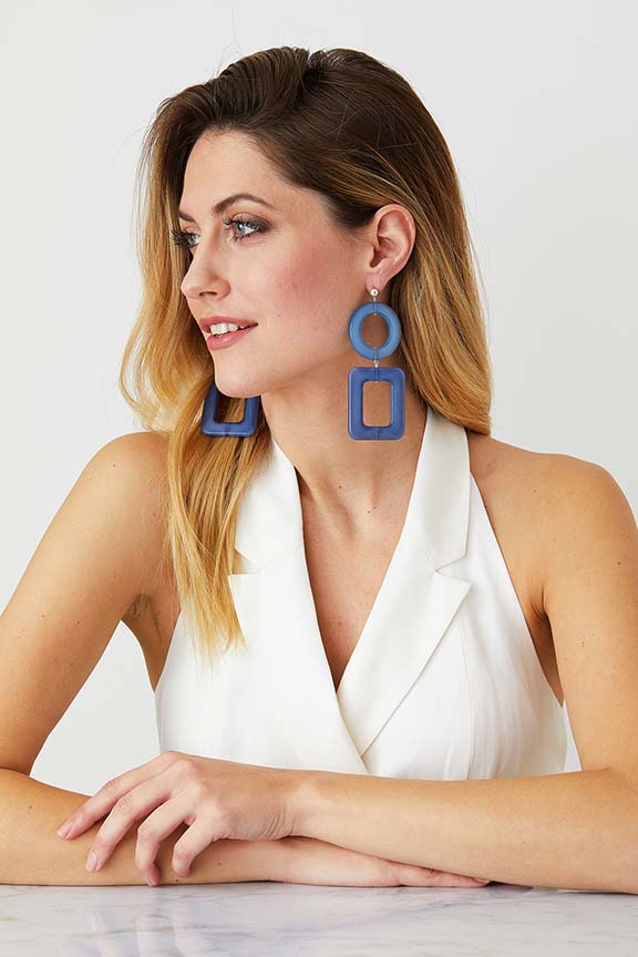 Blue statement earrings worn by a model in a white blazer