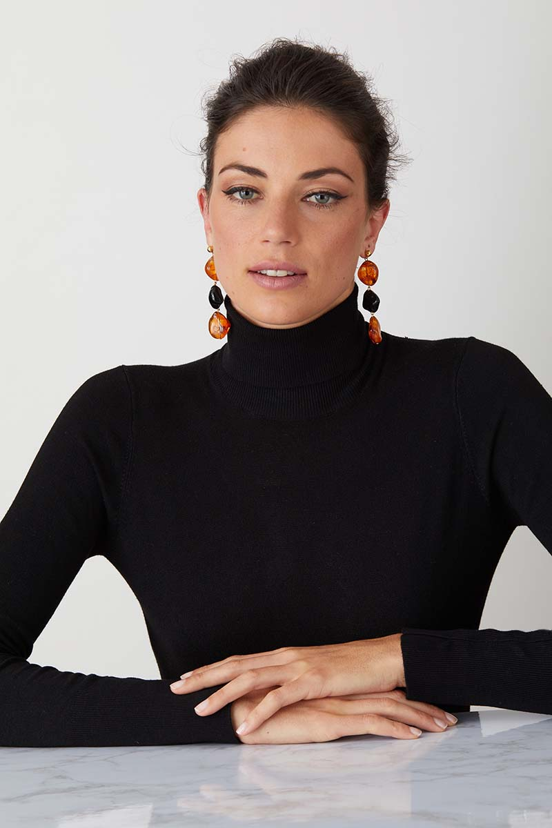 Amber black statement earrings worn by a model in a black turtleneck
