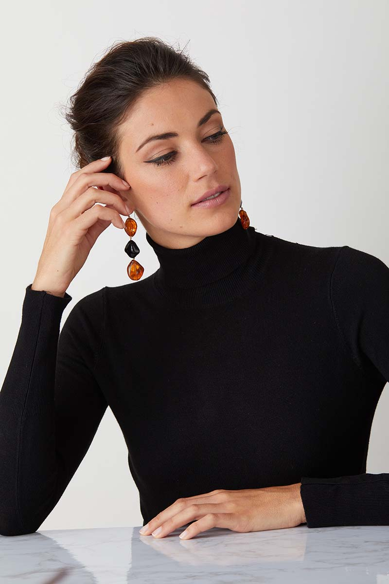 Amber black resin statement earrings worn by a model in a black turtleneck