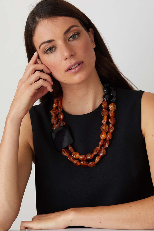 Amber black statement necklace worn by a model in a black evening dress
