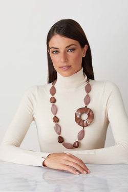 Beige brown statement necklace worn by a model in a white turtleneck