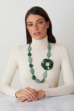 Green statement necklace worn by a model in a white turtleneck