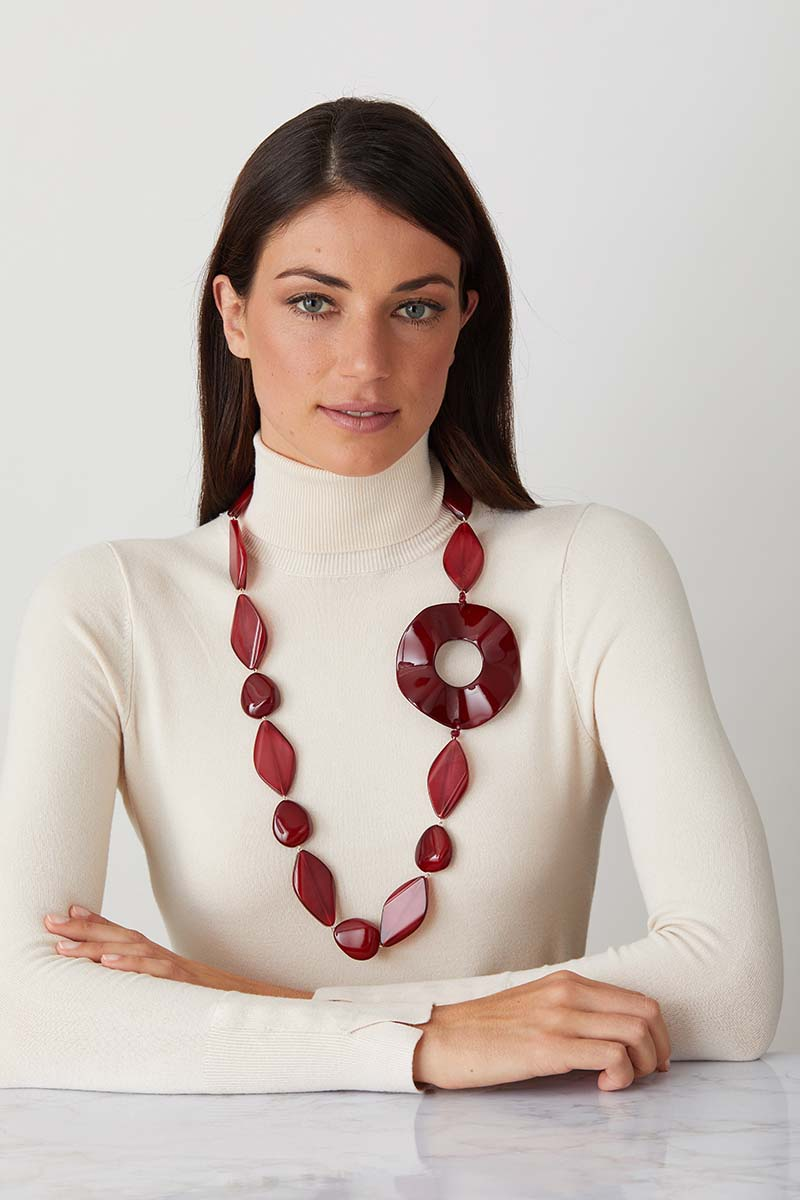 Red ruby statement necklace worn by a model in a white turtleneck