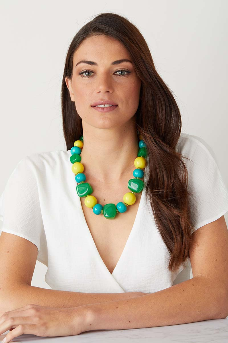 Green yellow blue statement necklace worn by a model in a white top. Resin necklace.