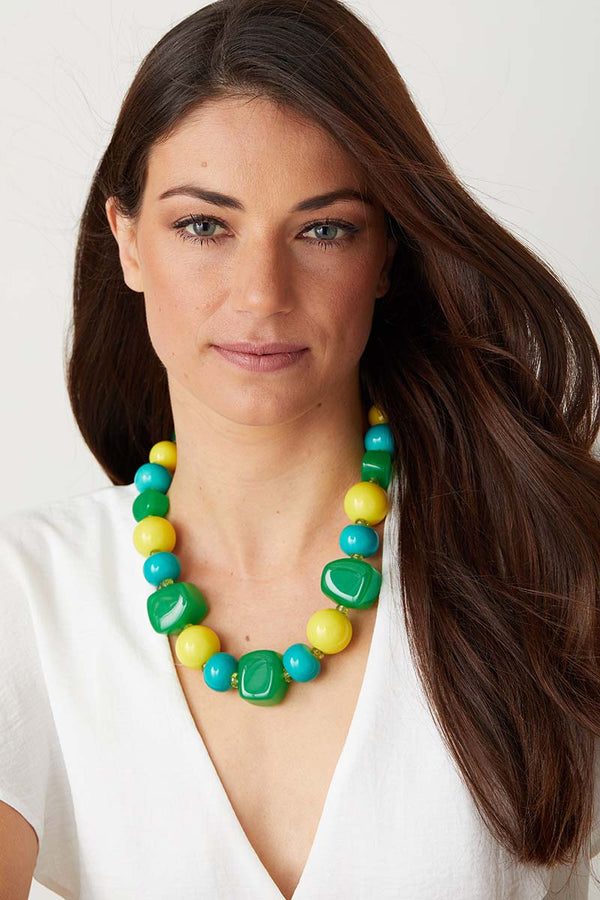 Green yellow blue statement necklace worn by a model in a  white top