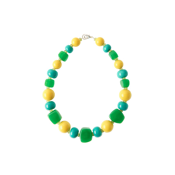Green yellow blue statement necklace worn by a model in a