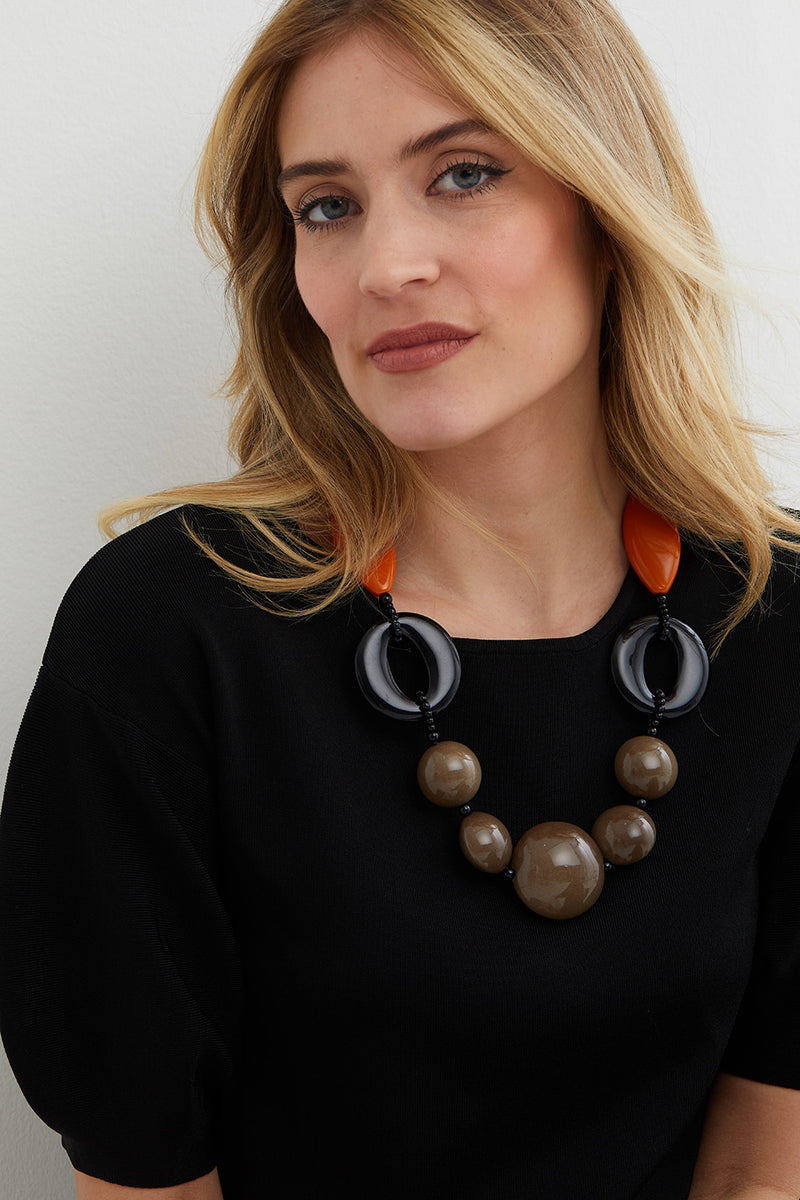 Black orange brown statement necklace worn by a model a black top