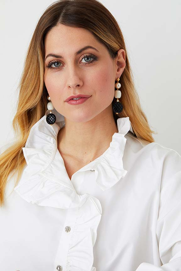 Pearl black white long statement necklace worn by a model in a white ruffled shirt