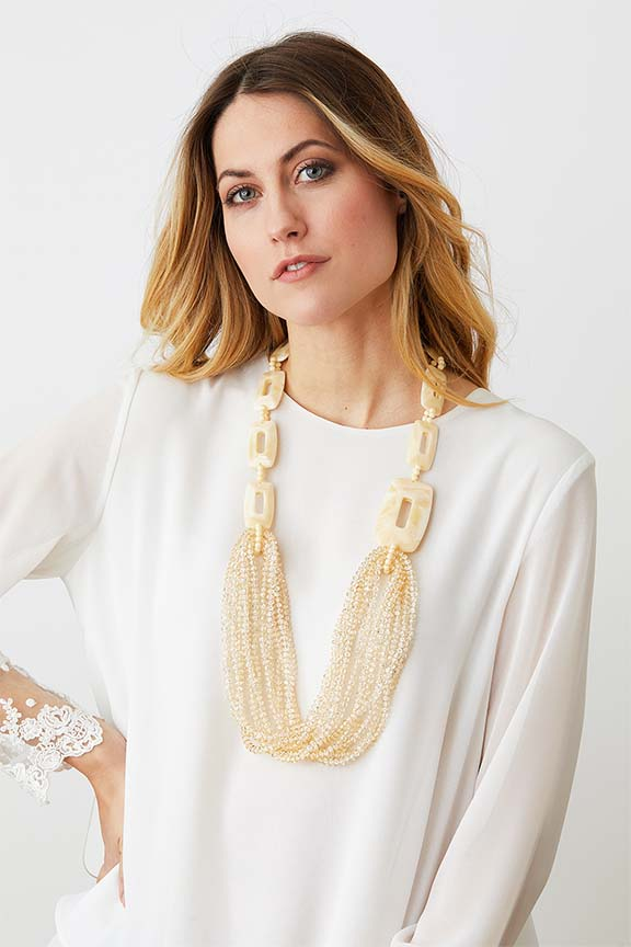 Ivory cream long crystal statement necklace worn by a model in a  white laced top