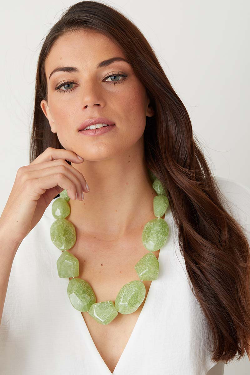 Light green statement necklace worn by a model in a  white top