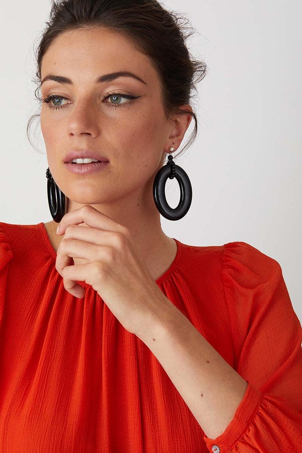 Black hoop statement earrings worn by a model in a flowy red dress