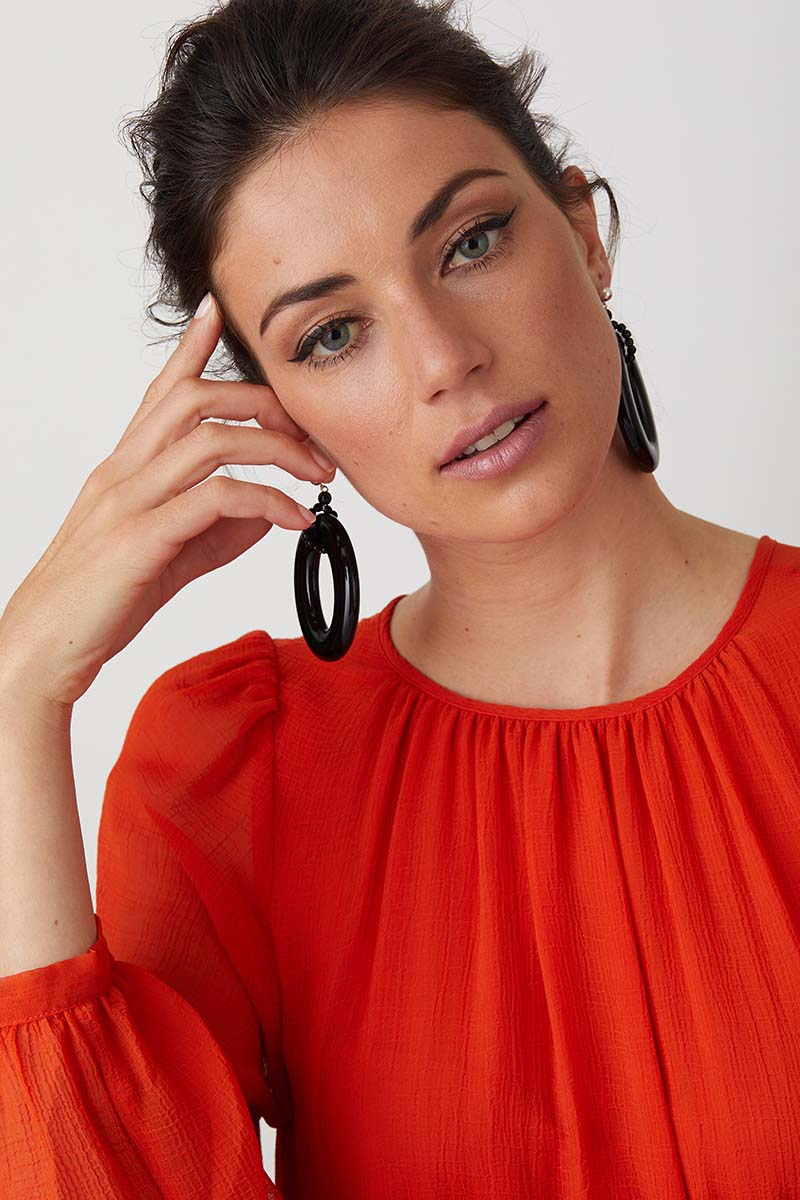 Black hoop resin statement earrings worn by a model in a red dress
