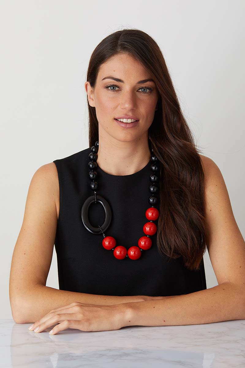 a luxury Italian black and red statement necklace made of resin worn by a woman in a black evening dress