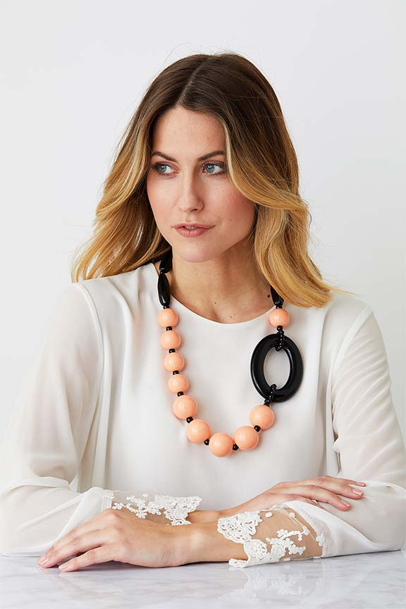 Pink black statement necklace worn by a model in a white laced top