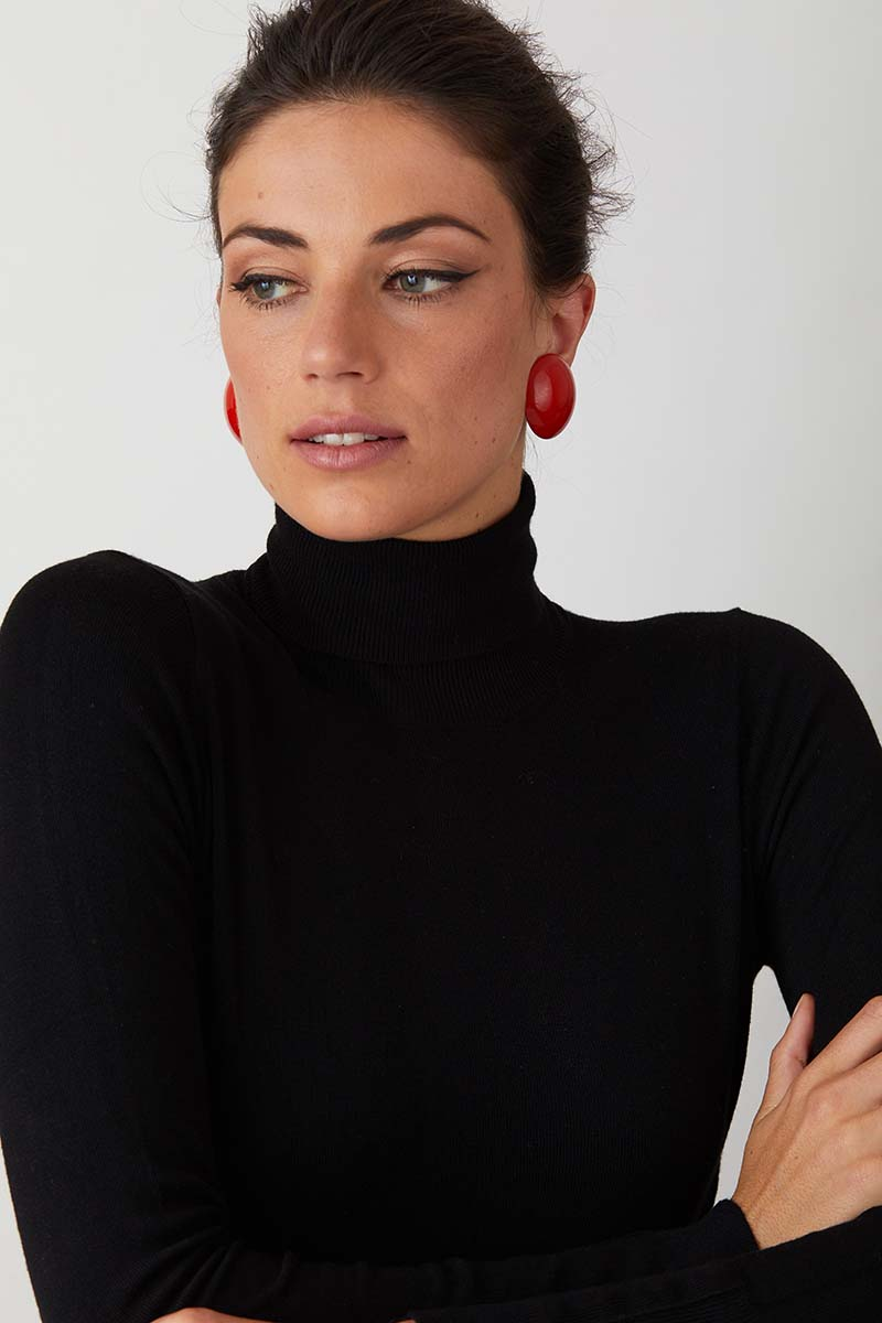 Red clip on button statement earrings worn by a model in a black turtleneck