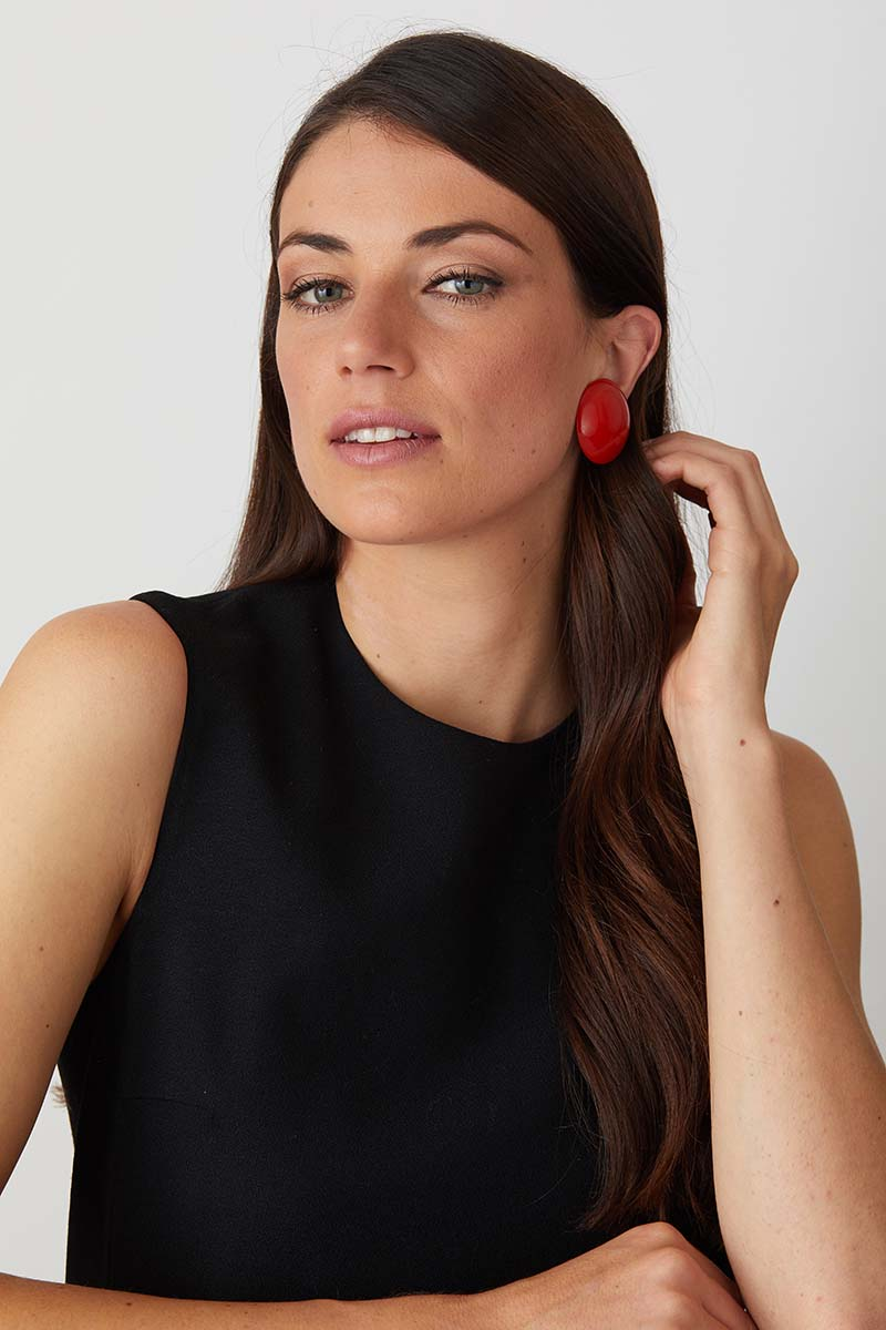 Red resin clip on button statement earrings worn by a model in a black evening dress. Comfort Clips designed by Pietrasanta