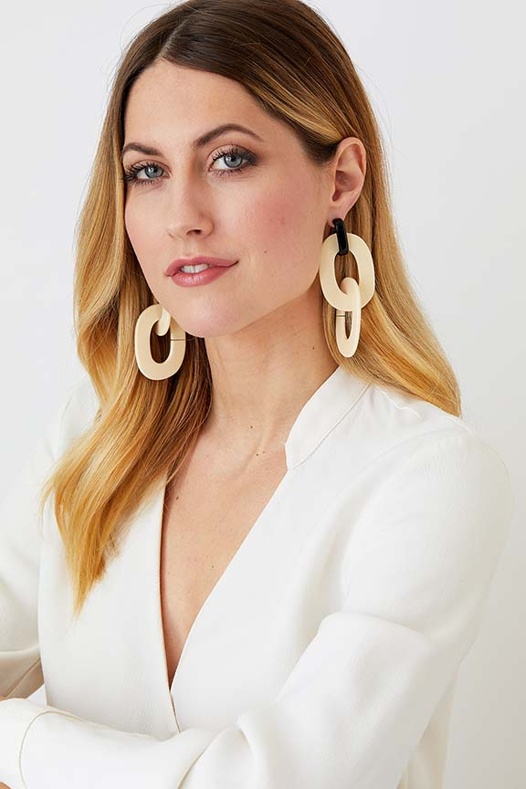 Cream black hoop statement earrings worn by a model in a white blazer