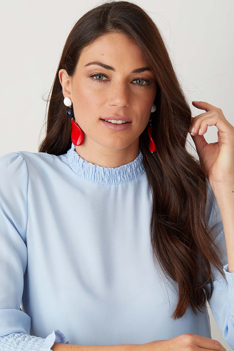 White red blue statement earrings worn by a model in a blue top