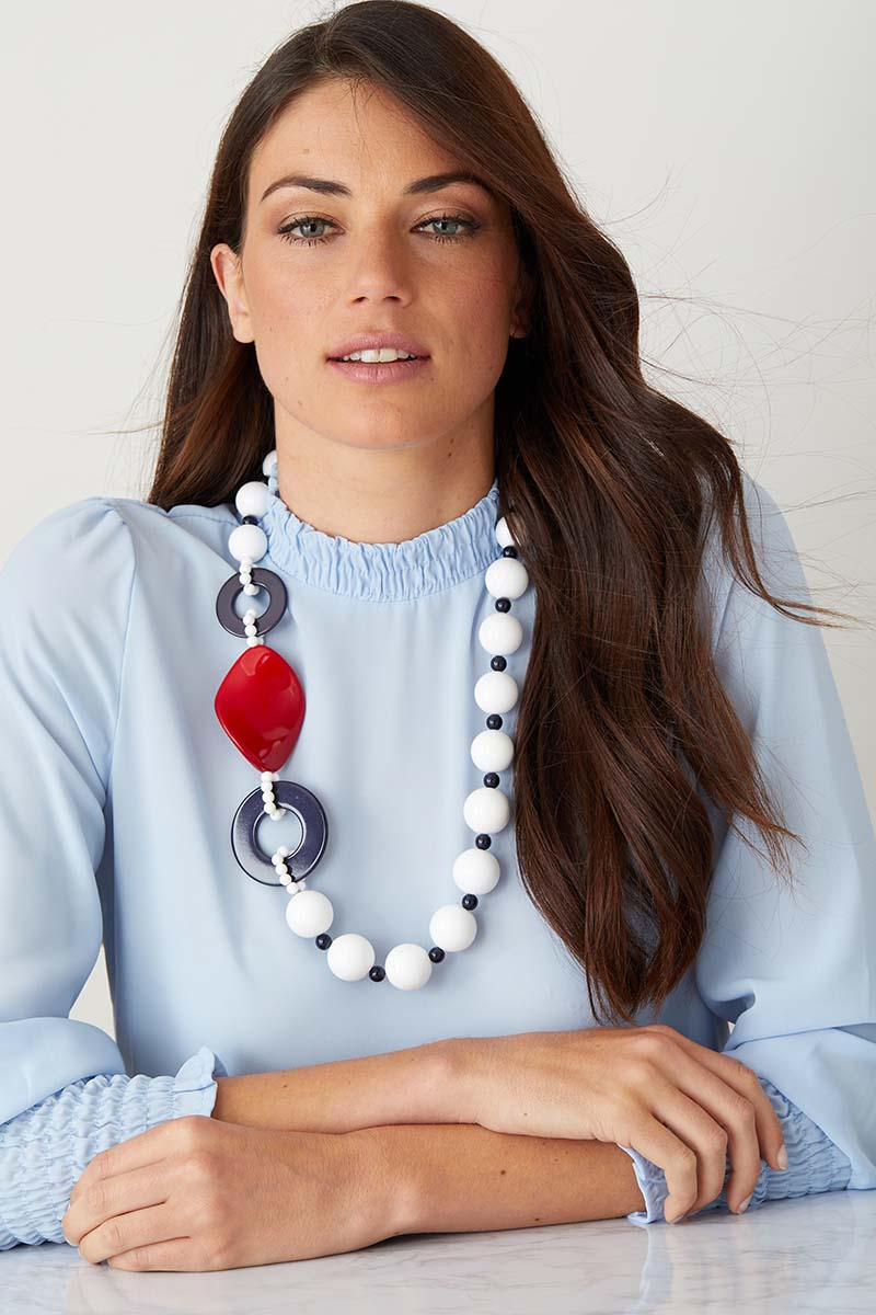 White red blue statement necklace worn by a model in a blue top