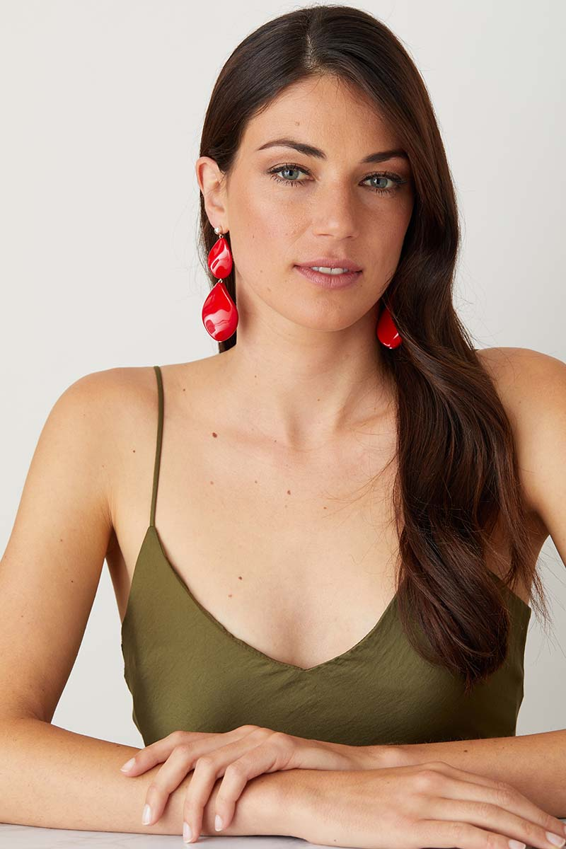 Red statement earrings worn by a model in a green summer dress