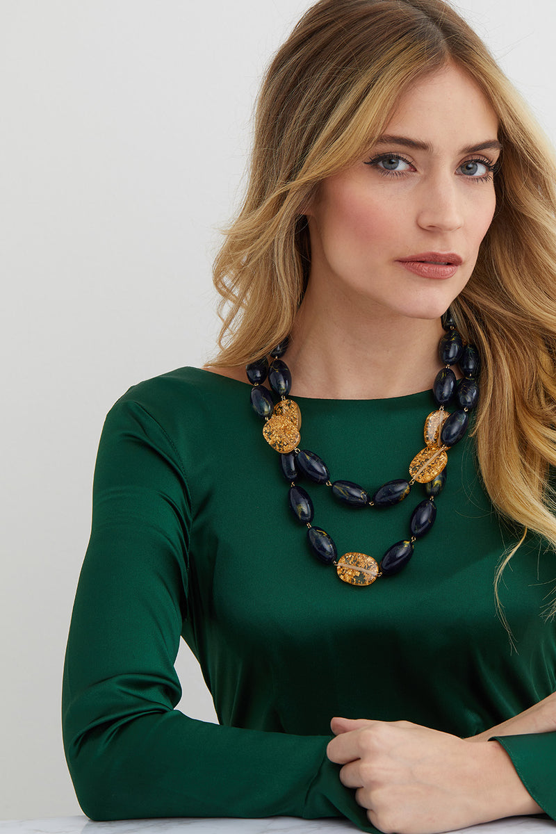 Green and gold statement necklace worn by a model in a green silk dress