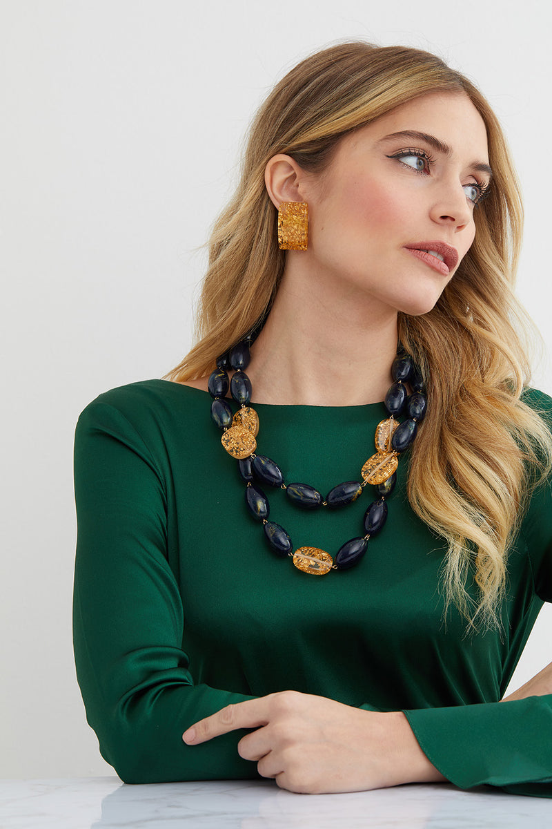 Green and gold statement pendant set worn by a model in a green silk dress