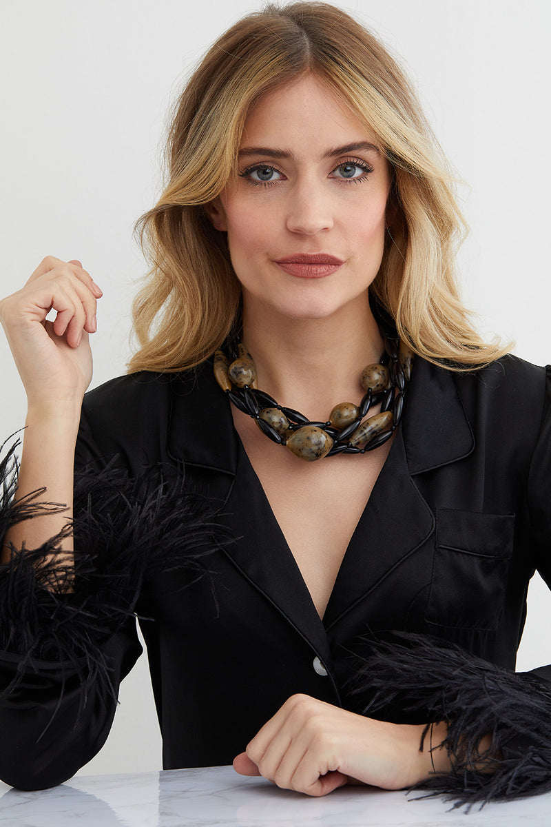 black and brown torchon statement necklace worn by a model in a silk black feathered top