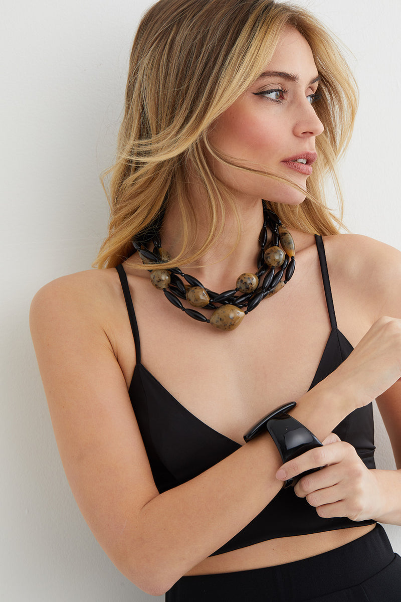 black and brown torchon statement necklace worn by a model in a silk black top