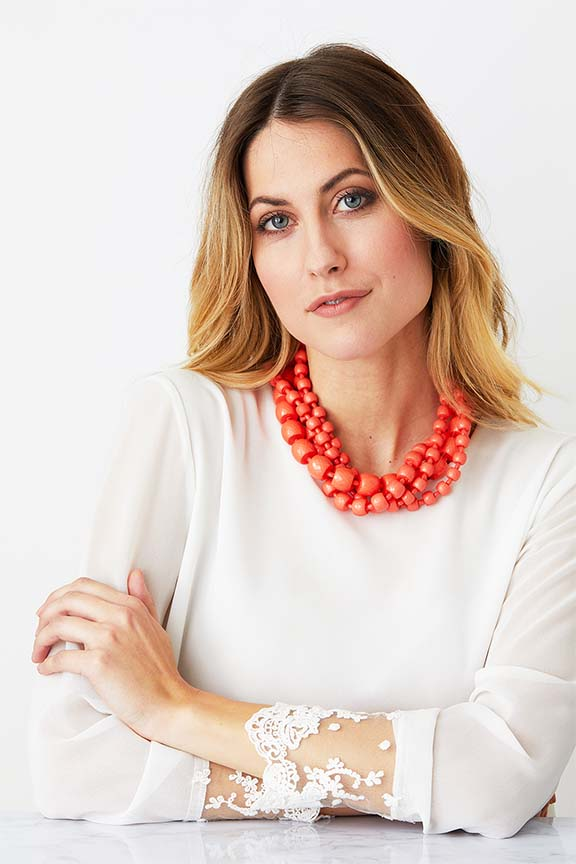Orange coral torchon statement necklace worn by a model in a white top