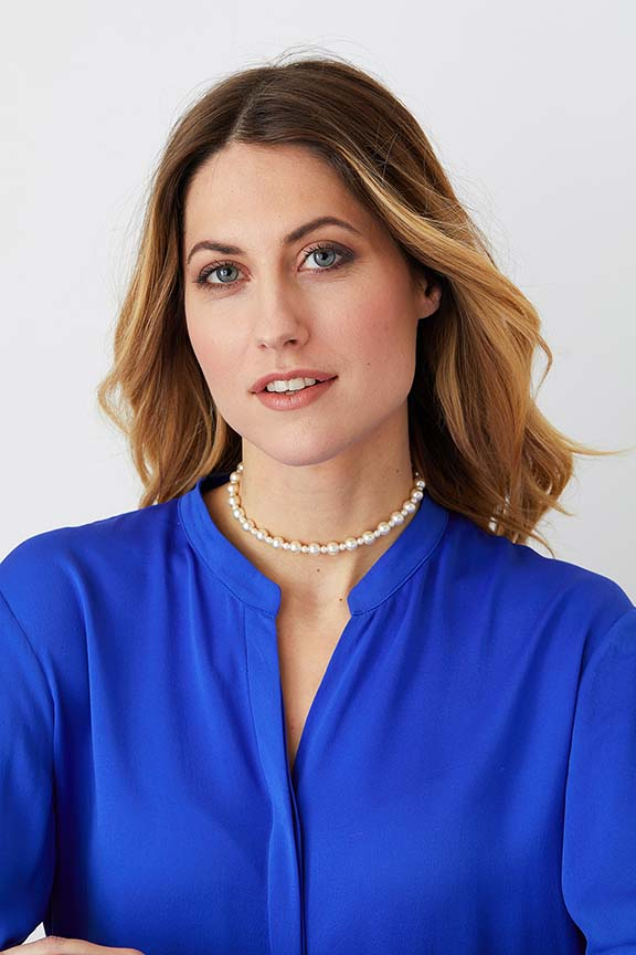 Pearl choker statement necklace worn by a model in a blue shirt