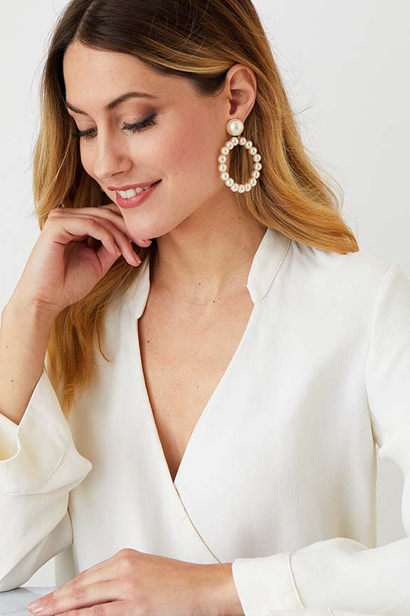 Pearl hoop clip on stud statement earrings worn by a model in a white blazer