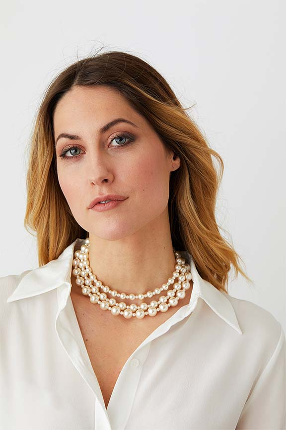 Pearl triple choker statement necklace worn by a model in a white silk collared shirt